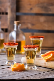Mezcal mexicain ou mescal tourné avec du piment rouge et une tranche d'orange. boisson alcoolisée similaire à la tequila