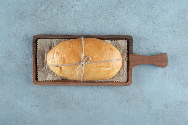Miche de pain attachée avec une corde sur planche de bois.