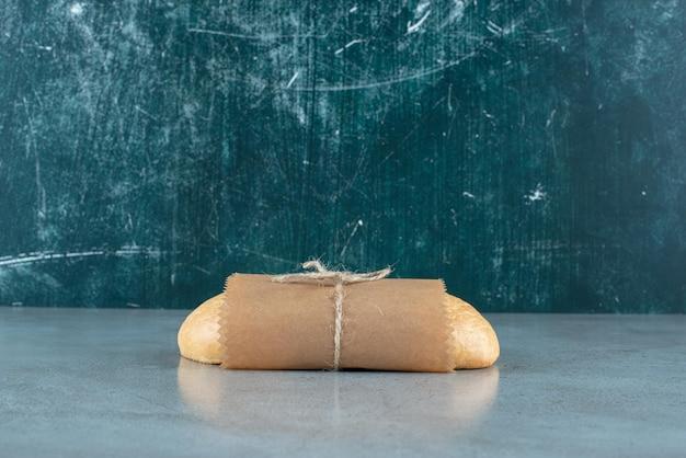 Miche de pain attachée avec une corde sur une surface en marbre.