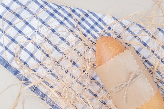Miche de pain blanc en corde sur nappe