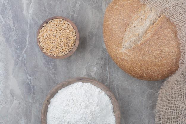 Une miche de pain blanc avec des grains d'avoine et de la farine sur une surface en marbre