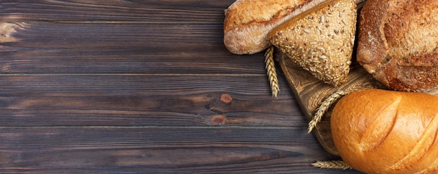 Miche de pain de blé cuit au four sur fond en bois.