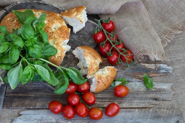 Une miche de pain cassée, tomates et basilic se bouchent