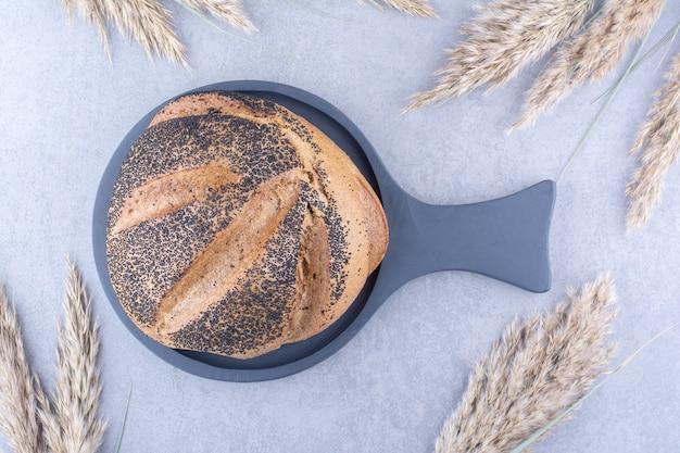 Miche de pain enduit de sésame noir sur un plat de service, à côté de tiges de plumes séchées sur une surface en marbre