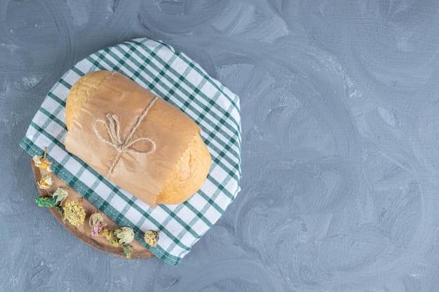 Miche de pain enveloppé sur une planche décorée de fleurs séchées sur table en marbre.