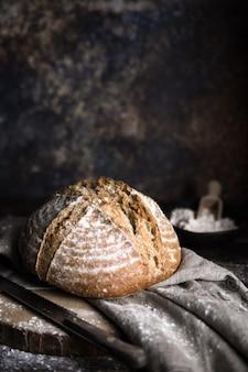 Une miche de pain fait maison sur une table en bois et un morceau de tissu gris