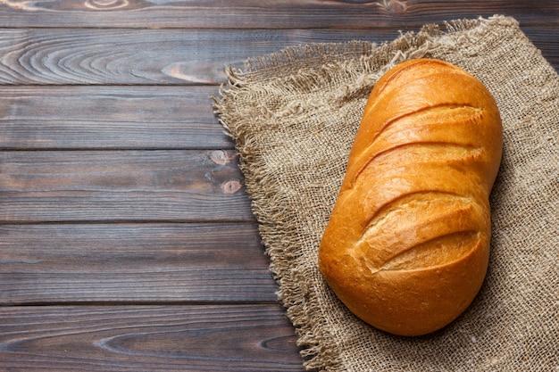 Miche de pain sur fond en bois, gros plan de nourriture