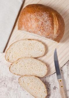 Miche de pain fraîchement cuit au four avec des morceaux sur planche de bois sur planche de bois avec un torchon et un couteau