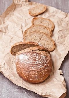 Miche de pain fraîchement sorti du four avec des morceaux sur une planche en bois blanche
