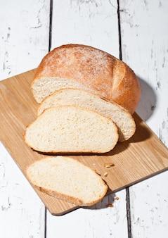 Miche de pain fraîchement sorti du four avec des morceaux sur planche de bois en bois blanc