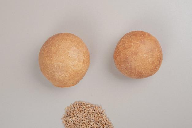 Miche de pain frais avec des grains d'avoine sur une surface blanche