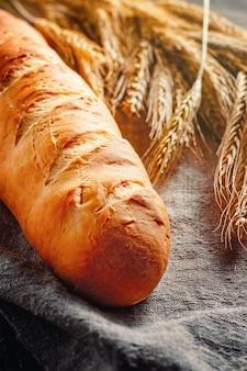 Miche de pain maison fraîche sur un fond sombre avec des épillets de seigle