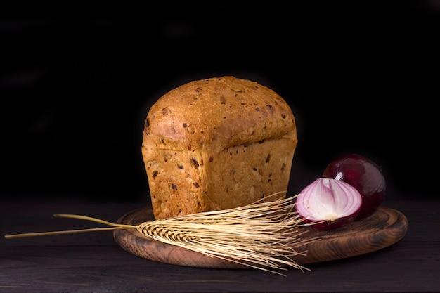 Miche de pain à l'oignon fraîchement cuit sur fond sombre