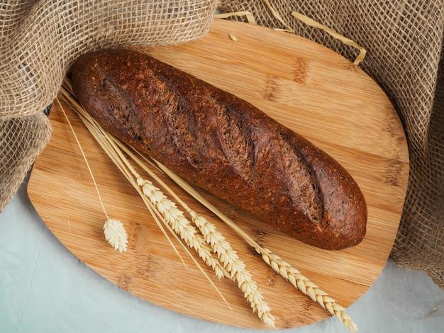 Miche de pain avec des oreilles se trouve sur une planche de bois