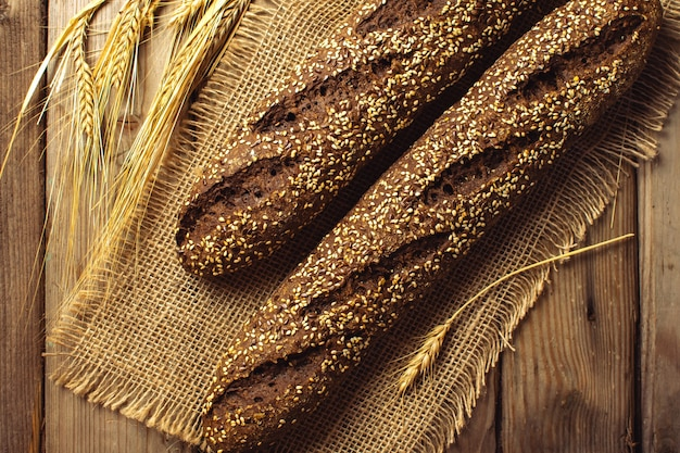 Miche de pain et oreilles de seigle nature morte sur fond rustique