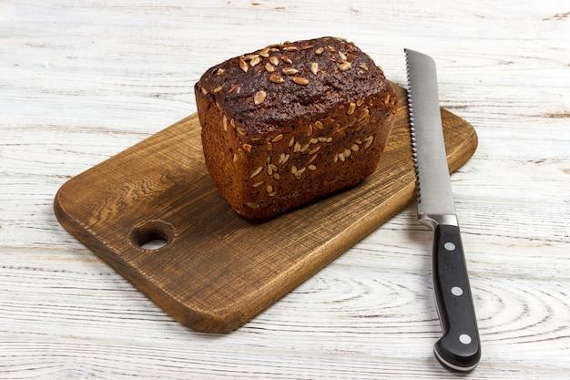 Une miche de pain sur une planche à découper avec un couteau