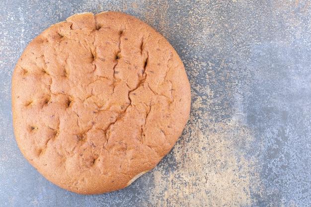Miche de pain plat et rond sur une surface en marbre