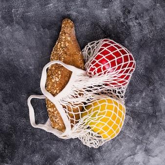 Miche de pain; poivron rouge et jaune dans un sac en filet blanc sur un fond texturé