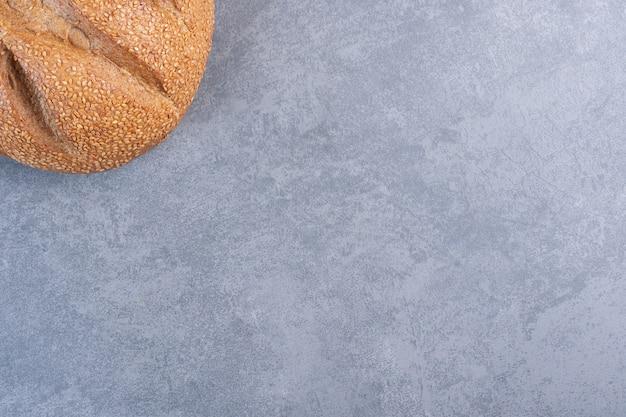 Miche de pain recouverte de graines de sésame sur marbre.