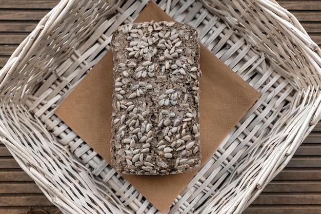 Une miche de pain repose dans un panier beige sur une table en bois.