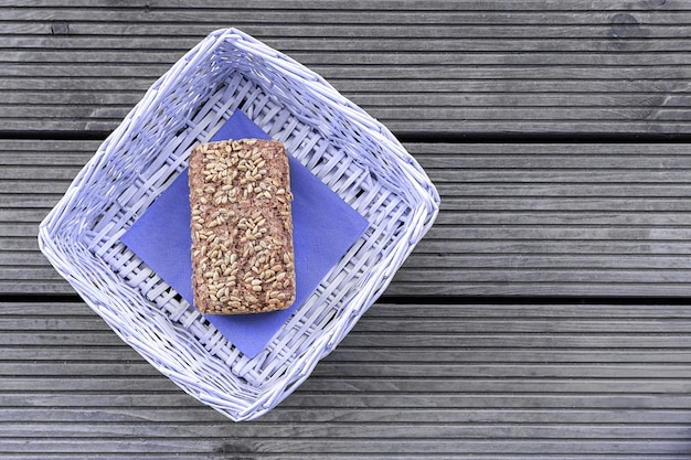 Une miche de pain repose dans un panier violet sur une table en bois.