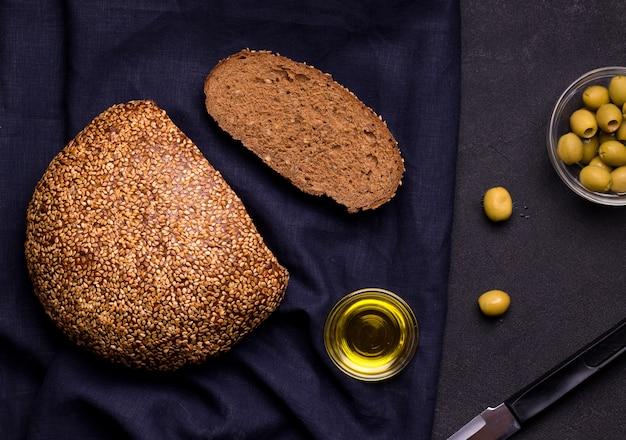 Miche de pain ronde aux graines de sésame sur lin bleu
