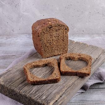 Miche de pain de seigle et deux tranches avec des trous sculptés en forme de coeur en eux sur une vieille planche de bois sur une table en bois gris.