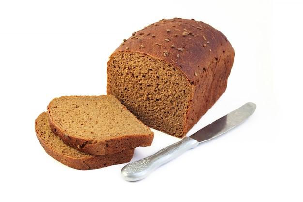 Miche de pain de seigle avec des tranches et un couteau