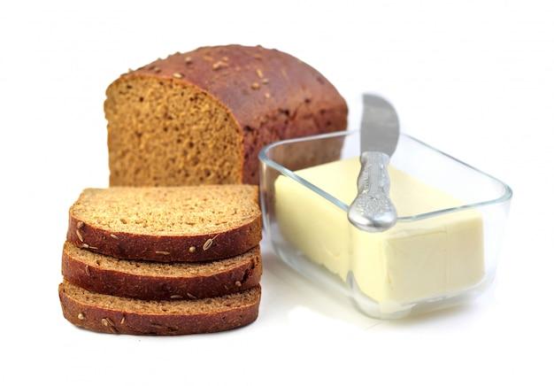 Miche de pain de seigle avec des tranches et du beurre dans un récipient en verre
