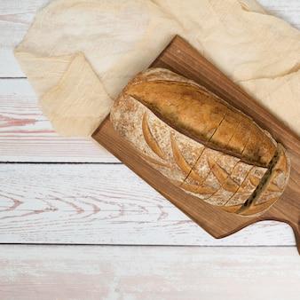Miche de pain avec des tranches sur une planche à découper et une nappe sur le bureau en bois