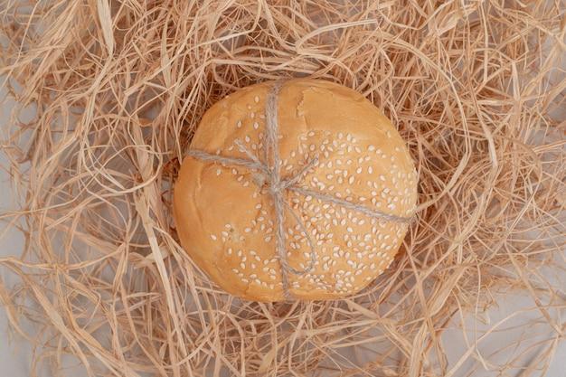 Miche de petit pain burger en corde sur surface blanche