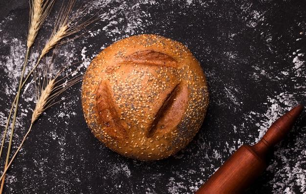 Miche ronde de pain blanc avec des graines de sésame et de pavot sur un espace noir avec de la farine