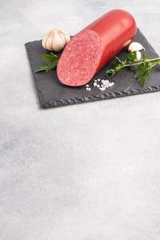 Une miche de saucisse de salami sur une coupe noire sur fond clair