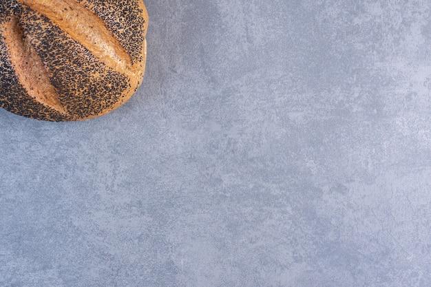 Miche unique de pain enrobé de sésame noir sur marbre.