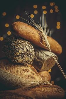 Miches de pain frais avec du blé et du gluten sur une table en bois
