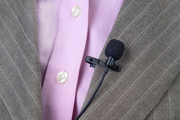 Le micro cravate est fixé avec un clip sur la veste, gros plan. enregistrement audio du son de la voix sur un microphone à condensateur.