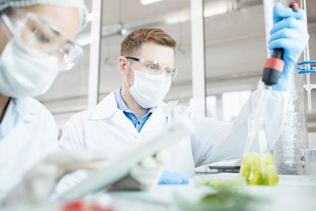 Microbiologiste prenant un échantillon de solution dans un flacon