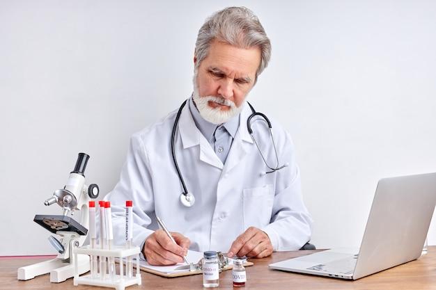 Microbiologiste principal avec un tube d'échantillons biologiques contaminés par le coronavirus