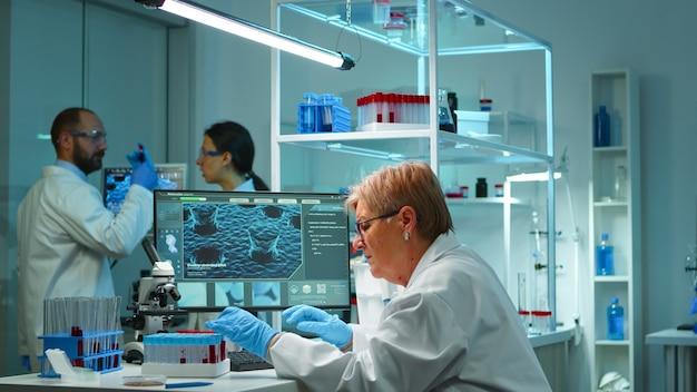 Microchimiste faisant des recherches la nuit en vérifiant le liquide sanguin dans un tube à essai en tapant les résultats sur un ordinateur dans un laboratoire moderne équipé. examen de l'évolution du virus à l'aide de la haute technologie pour le développement d'un vaccin contre covid19