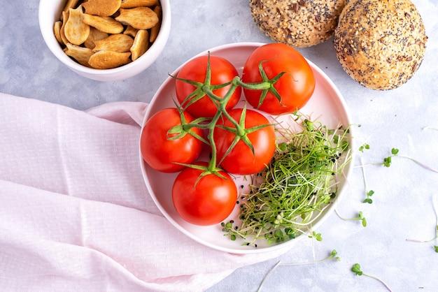 Les microgreens aux tomates sur une assiette blanche et une assiette blanche avec des biscuits et des petits pains aux céréales.