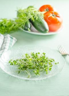 Microgreens sur plaque avec des légumes en arrière-plan, concept de régime alimentaire végétalien sain