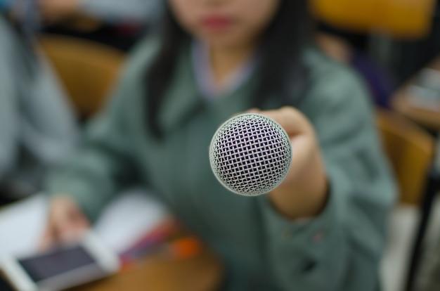Microphone avec l'arrière-plan flou d'une femme tenant