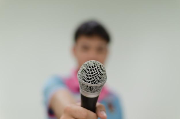 Microphone avec l'arrière-plan flou d'un homme tenant un micro