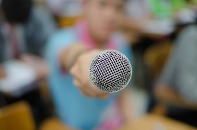 Microphone avec l'arrière-plan flou d'un jeune homme