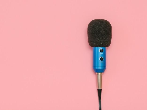 Le microphone bleu avec le fil sur une table rose