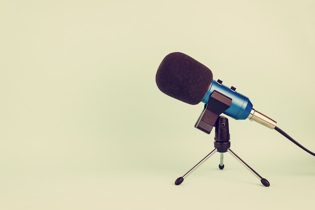 Microphone bleu avec fil sur ton pastel dans un style vintage.