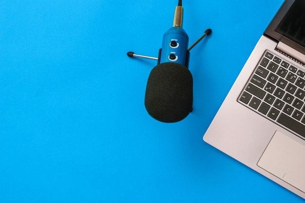 Microphone bleu avec ordinateur portable sur fond bleu. le concept d'organisation du travail. matériel d'enregistrement, de communication et d'écoute de musique. mise à plat.