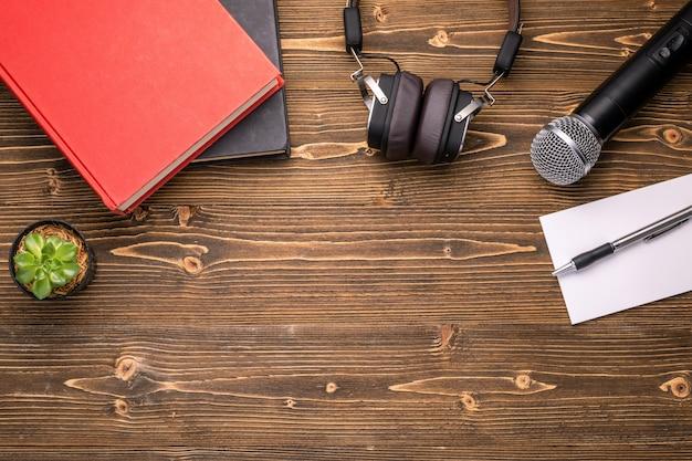 Microphone, casque, livre et note papier sur planche de bois marron. apprendre à parler le concept