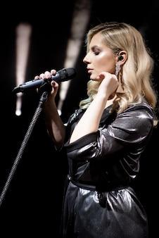 Microphone et chanteuse se bouchent. femme chantant dans un microphone.