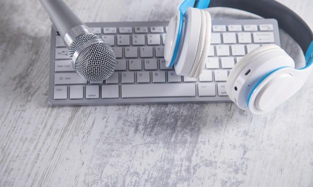 Microphone, clavier et écouteurs sur un bureau blanc.